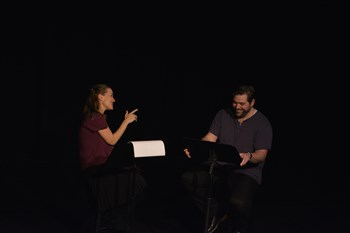 Two actors perform in a dark space